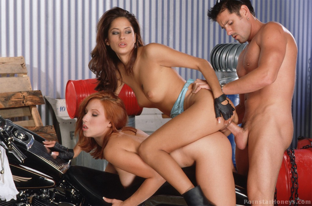 Aroused red hair temptress with shaved pussy is having hot threesome in  garage