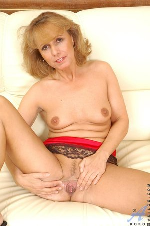 Mature blonde sofa sits