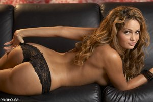 Steaming hot chick teases with her indulging body on a black couch before she peels off her red and black corset and reveals her juicy boobs then pulls down her black panty and bares her sweet pussy in different poses wearing her black stockings and