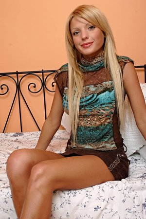 Sweet long-legged chick with long blonde hair is taking off clothes