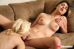 Perfect brunette with belly ring and blonde friend with smooth skin lays on the brown suede sofa