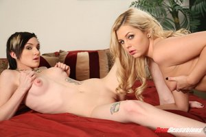 Tattooed brunette butch wearing chained necklace plays around with innocent blonde coworker on the red bed