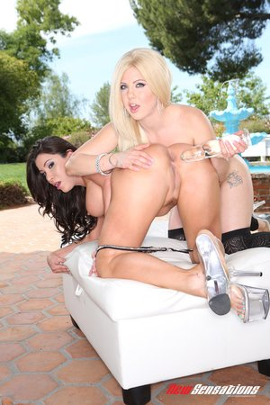 Busty brunette and young blonde in matching leopard printed lingerie enjoy playing with fleshy dildo by the pool outdoors