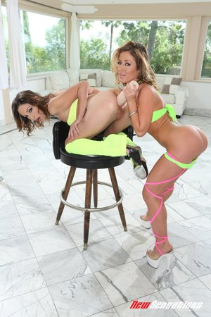 Short haired brunette with tiny tits wearing yellow gets frisky with blonde cougar in sexy haltered green bikini in the living room