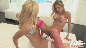 Delicious young blonde hotties in blue and pink two piece bikinis and fishnet stockings play with crystal dildo outdoors