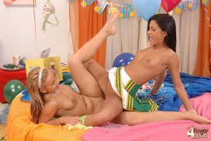 Lesbian brunette and blonde cheerleaders wearing headbands and socks enjoys lesbian fun on the colorful bed with peach dildo near balloons