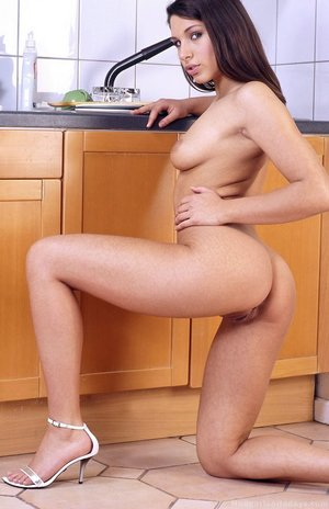Lying on the kitchen floor she fucks her tight anus with a toy digging deep
