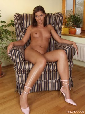 Kneeling in a striped chair she poses topless flashing a cute smile