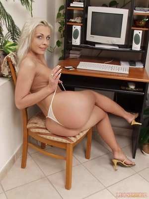 Blonde wearing white shorts she strikes sensual poses in her office