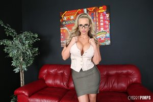 Blonde slut wearing sexy glasses gets fucked hard from behind on red couch