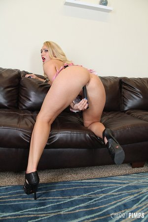 Blonde woman with sexy high heels on uses a black toy deep in her pink pussy