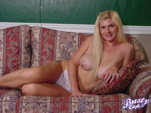 Innocent looking blonde with pierced pink nipples lays on the vintage sofa reading a book while wearing white sheer thong