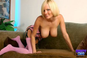 Short haired blonde with blue eyes opens her pink furry vest and lays on the gray couch wearing pink stockings